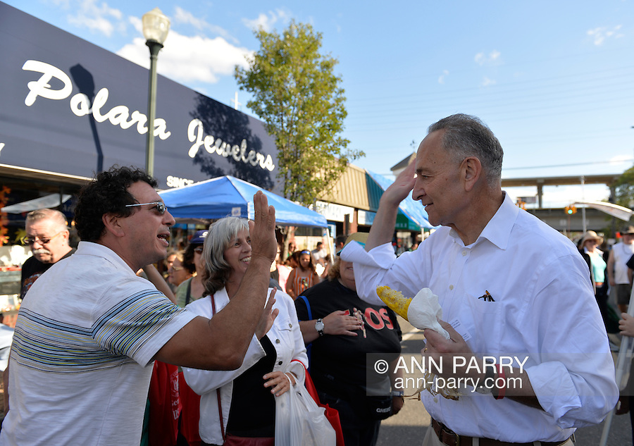 """Bellmore, New York, U.S. 22nd September 2013. U.S. Senator CHARLES """"CHUCK"""" SCHUMER  (Democrat), running for re-election in November, and a man slap """"high five"""" while talking to each other during the senator's campaign visit at the 27th Annual Bellmore Festival, featuring family fun with exhibits and attractions in a 25 square block area, with over 120,000 people expected to attend over the weekend."""