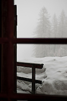 A blizzard creates great drifts of snow beyond the window