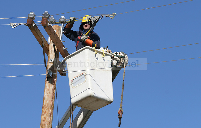Employees work to restore electricity to the community of East Bernstadt in Laurel County, Ky. on March 3 following the March 2, 2012 tornado in which five people in the county were killed. Photo by Latara Appleby | Staff ..