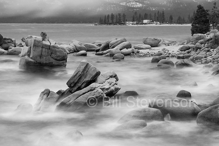 A black and white photo of Lake Tahoe. This was a windy day and the waves were rolling in over the rocks. The shutter was left open for about a minute and this accounts for the blurred, misty look.