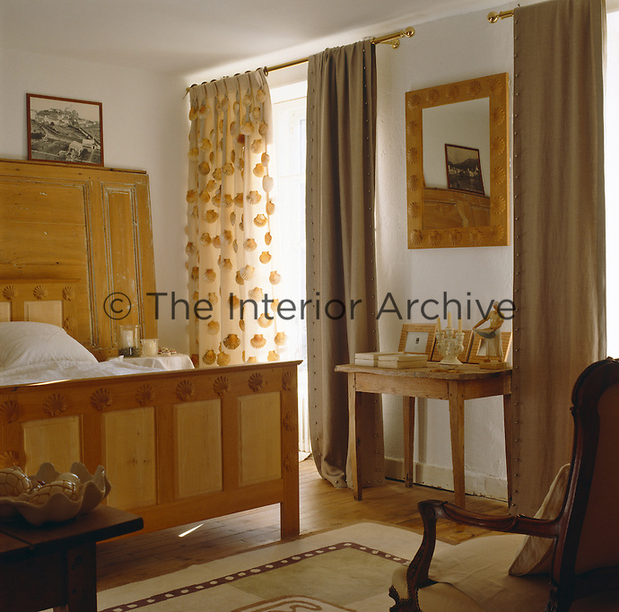 This rustic bedroom has a scallop theme with real shells sewn to the sheer curtains and a scallop motif  used to decorate the wooden bed and the frame of the mirror