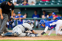 Malcolm Holland (5) of the Great Lakes Loons slides across home plate ahead of the tag by West Michigan Whitecaps catcher Adolfo Reina (20) at the Dow Diamond on June 11, 2013 in Midland, Michigan.  The Loons defeated the Whitecaps 13-6.  (Brian Westerholt/Four Seam Images)