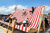 Amsterdam Kookt festival. Amsterdam Kookt is een festival met foodtrucks en muziek op het NDSM terrein. Kinderen en volwassenen zitten in een reuze strandstoel