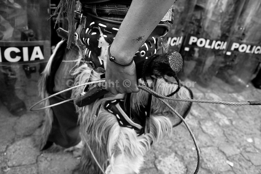 An Indian, holding a steel wire whip, stands in front of the riot police block during the Inti Raymi (San Juan) festivities in Cotacachi, Ecuador, 29 June 2010. 'La toma de la Plaza' (Taking of the square) is an ancient ritual kept by Andean indigenous communities. From the early morning of the feast day, various groups of San Juan dancers from remote mountain villages dance in a slow trot towards the main square of Cotacachi. Reaching the plaza, Indians start to dance around. They pound in synchronized dance rhythm, shout loudly, whistle and wave whips, showing the strength and aggression. Dancers from either the upper communities (El Topo) or the lower communities (La Calera), joined in respective coalitions, seek to conquer and dominate the square and do not let their rivals enter. If not moderated by the police in time, the high tension between groups always ends up in violent clashes.
