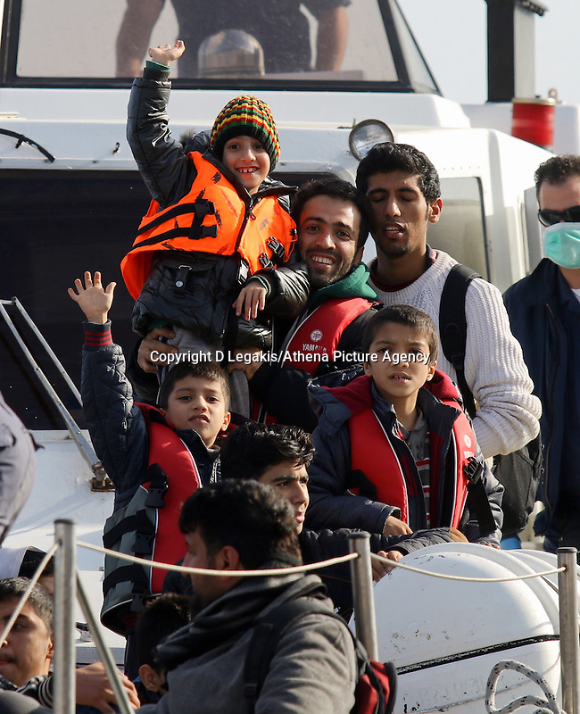 Pictured: Young boys are cheering on as the Coastguard vessel carrying them to safety approaches Ierapetra Thursday 27 November 2014<br />