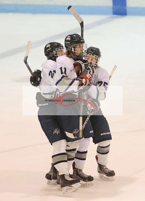 Eagle River's Sutton McDonald, center, is mobbed by teammates Connor Canterbury (24), and Ben Rinckey (75) following his third-period goal at Ben Boeke Arena Tuesday, February 2, 2016.  Photo for the Star by Michael Dinneen