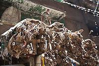 2011 Mokattam Garbage City (alla periferia del Cairo) il quartiere copto dove si vive in mezzo alla spazzatura raccolta: un uomo lavora sopra ad un cumulo di carta e cartone.