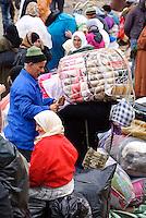 Un uomo aiuta una donna marocchina, portarice di merci, a caricarsi la merce sulle spalle. Ceuta, 8 febbraio, 2010<br /> <br /> A man helps a moroccan women, goods bearers, to hoist the burden on the shoulders. Ceuta, February 8, 2010