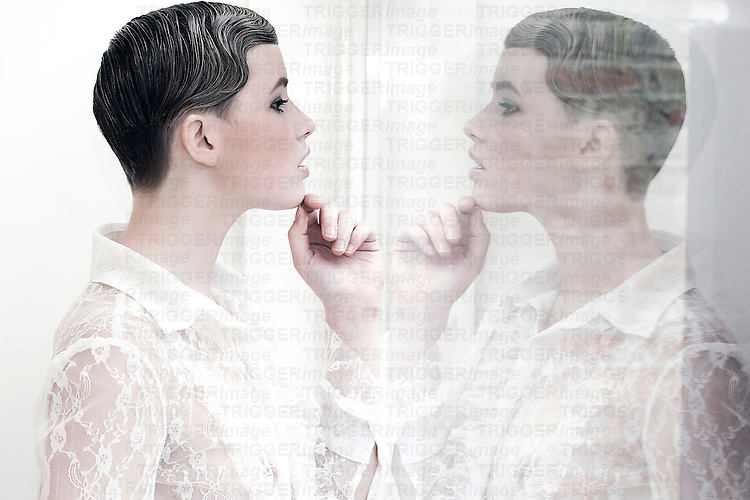 Young woman with short hair and pale features wearing white lace top looking into mirror reflection