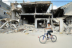An 11-year old boy rides his bike amid the ruins of Khan Yunis, Gaza. Houses in the area were destroyed by Israeli air strikes during the 2014 war between the state of Israel and the Hamas government of Gaza.