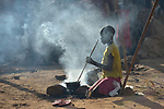 Eight-year old Adieu Anai cooks over a fire in a camp for more than 5,000 internally displaced persons in an Episcopal Church compound in Wau, South Sudan. Most of the families here were displaced by violence early in 2017, after a larger number took refuge in other church sites when widespread armed conflict engulfed Wau in June 2016.<br /> <br /> Norwegian Church Aid, a member of the ACT Alliance, has provided relief supplies to the displaced in Wau, and has supported the South Sudan Council of Churches as it has struggled to mediate the conflict in Wau. <br /> <br /> Parental consent obtained.