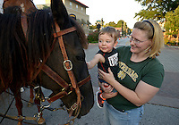 NWA Democrat-Gazette/BEN GOFF @NWABENGOFF<br /> Amanda DeBoer of Bentonville holds her son Leo DeBoer, 1, up to pet a re-enactors horse on Friday Sept. 4, 2015 after a re-enactment of an 1893 bank robbery during First Friday September: Sugar Creek Days on the Bentonville square. The re-enactment was based on the June 5, 1893 robbery in which outlaw Henry Starr and five men made off with cash from the People's Bank of Bentonville after a shootout with civilians and the sheriff.