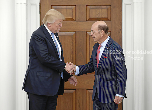 United States President-elect Donald Trump (L) shakes hands with investor Wilbur Ross at the clubhouse of Trump International Golf Club, in Bedminster Township, New Jersey, USA, 20 November 2016.<br /> Credit: Peter Foley / Pool via CNP