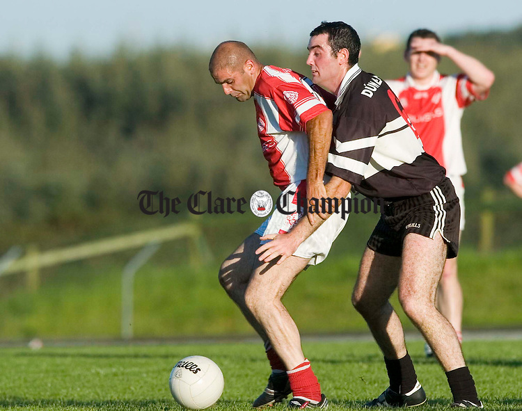 Cathal Shannon of Eie Og is tackled by Doonbeg's  David Downes during their game in Kilmihil.