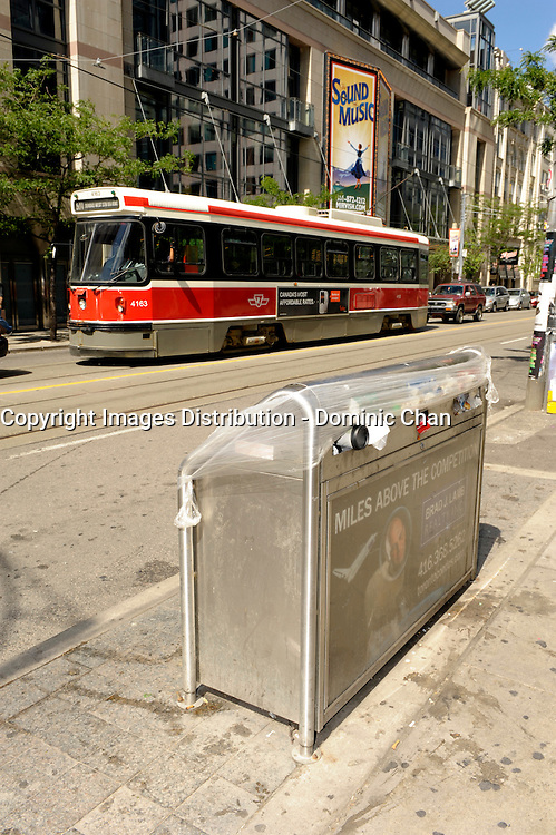 Toronto (on) CANADA, July 4, 2009  Toronto Garbage Strike - full garbage can on King Street / Entertainment District outside the Prince of Wales Theatre with TTC street car in the background.