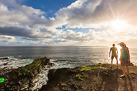 A man and woman hiking the Ka'ena Point trail pause to take in the view in the late afternoon sun, O'ahu.