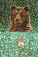 The mosaic wall tiles enclosing the shower in this ensuite bathroom include the depiction of a bear
