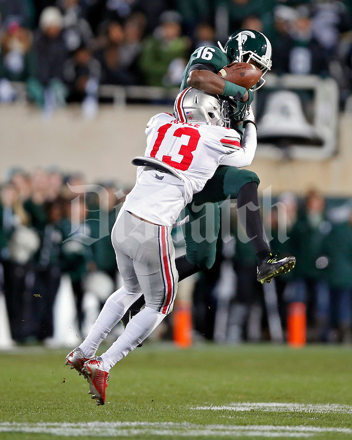 Michigan State Spartans wide receiver Aaron Burbridge (16) makes a catch against Ohio State Buckeyes cornerback Eli Apple (13) during the 1st quarter at Spartan Stadium in East Lansing, Michigan on November 8, 2014.  (Dispatch photo by Kyle Robertson)