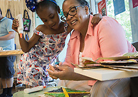 NWA Democrat-Gazette/CHARLIE KAIJO Jasmin Hamilton, 6, (left) hugs Olga Hamilton of Rogers as she works on an art project during a drop-in art making class, Sunday, July 7, 2019 at Crystal Bridges Museum in Bentonville. <br /> <br /> Guest artist, Michael Albert, showed guests how to make art using upcycled cardboard from discarded consumer packaging. The New York native is on a multi-state tour.