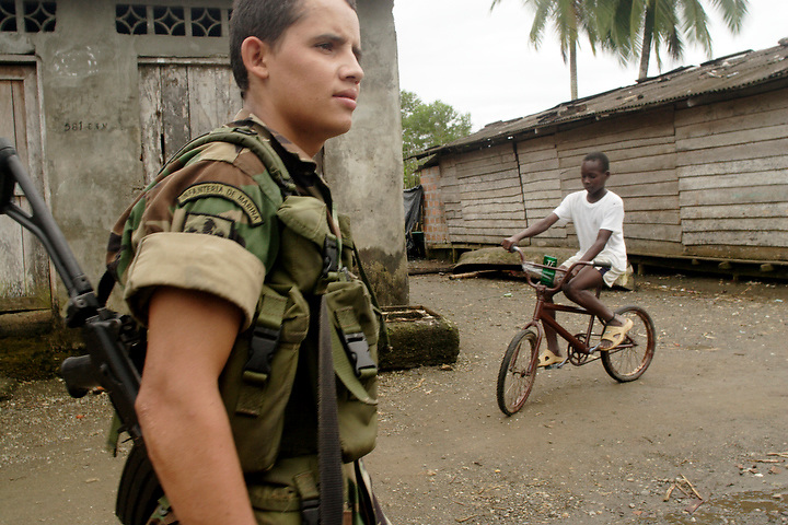 NUQUÍ, EL CHOCO, COLOMBIA -- DECEMBER 12:  19-year-old Colombian soldier Juan Idarraga Vasquez patrols the town of Nuqui on December 12, 2005. Nuquí is a small town on Colombia's isolated and untamed Pacific coast, an area sandwiched between endless miles of trackless rainforest and the Pacific Ocean. (Photo by Dennis Drenner/Aurora).
