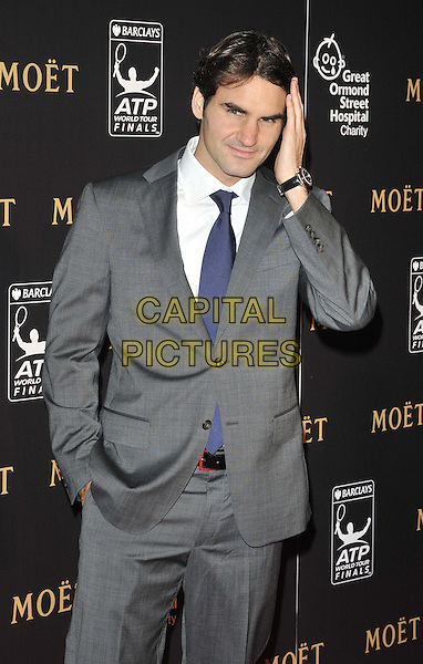Roger Federer.attended the Barclays ATP World Tour Finals official launch party, Battersea Power Station, Cringle St., London, England, UK, 17th November 2011..half  length grey gray suit  blue tie white shirt hand in pocket touching head .CAP/CAN.©Can Nguyen/Capital Pictures.