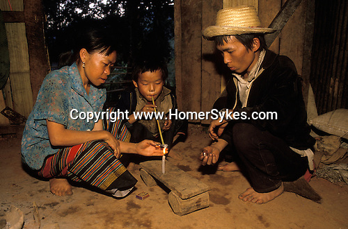 Northern Thailand. Thai family addicted to opium, their child smoking opium. Peasant farmers in home. The boy is 8 years old.