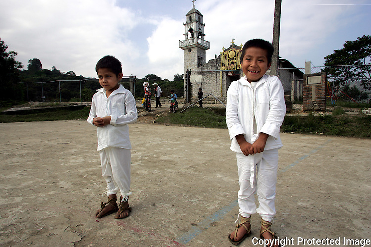 Naua Indian children stand next each other in front of the church of their village of Ayotzinapan, Puebla. Photo by Heriberto Rodriguez/ CGEIB