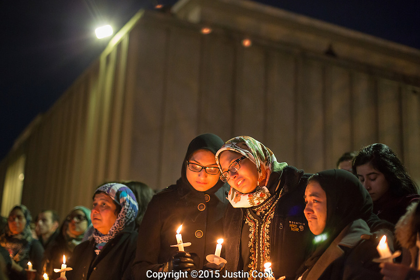 Nida Allam, (right) a senior at North Carolina State University, is comforted by Arsheen Allam as thousands gathered for a vigil and memorial for three shooting victims at The Pit at The University of North Carolina at Chapel Hill in Chapel Hill, North Carolina on Wednesday, February 11, 2015. Craig Hicks, 46, of Chapel Hill has been charged with three counts of first-degree murder in the killings of Deah Barakat, 23, a UNC student; his wife, Yusor Abu-Salha, 21; and her sister, Razan Abu-Salha, 19. (Justin Cook)