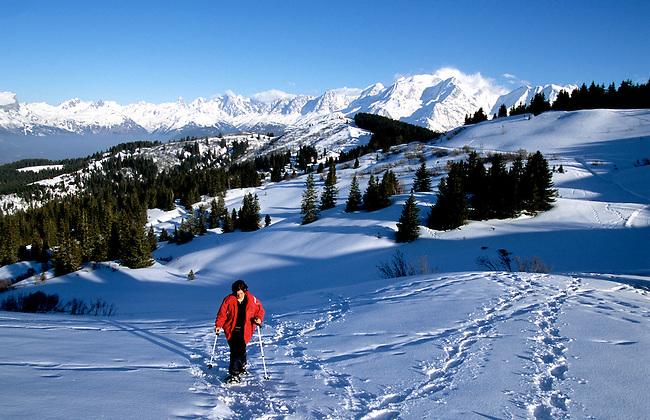France, Haute-Savoie. Randonnee en raquettes pres de Megeve. *** Woman snowshoeing near Megeve. Haute-Savoie, France