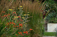 Vivid orange crocosmia, yarrow and grasses are grouped together in an informal bed next to a flight of stone steps