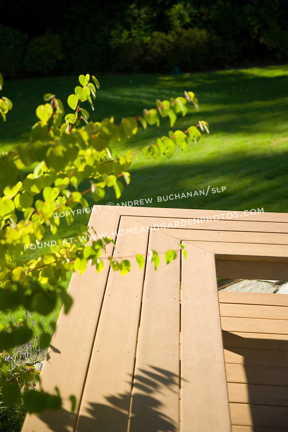 Detail of a bench seat  constructed of Trex brand composite decking on a sunny, summer scene of a raised, multi level residential deck with lawn beyond