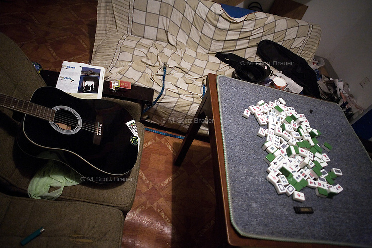 Mah Jongg tiles and a guitar lay unused as punk rock musicians leave an apartment gathering to find food late at night in Nanjing, China.