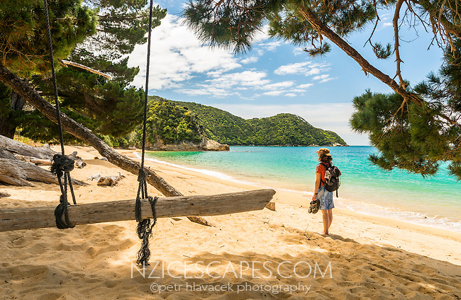 Young woman enjoying swing on Anatakapau Bay on Abel Tasman Coast Track, Abel Tasman National Park, Nelson Region, South Island, New Zealand
