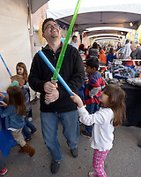 NWA Democrat-Gazette/BEN GOFF @NWABENGOFF<br /> Ximena Corpus, 5, and father Javier Corpus of Bentonville have a lightsaber duel in the Hasbro booth on Friday Nov. 6, 2015 during Downtown Bentonville, Inc.'s First Friday: Toyland on the Bentonville Square. Walmart toy vendors displayed a variety of their new offerings at the event ahead of the holiday shopping season.