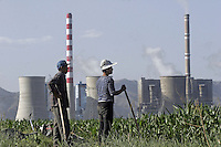 Two Chinese farmers stand beside their corn field close to the Shengtou No. 2 Power Plant near Shuozhou, Shanxi Province, China. Power plants such as this one in China's rural provinces in the north supply over two thirds of Beijing's electricity and suffers environmental pollution and even local brown-outs to guarantee the capital's power demand..