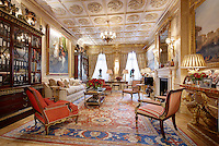 An opulent library sitting room with an ornate plasterwork ceiling. The windows are dressed with floor to ceiling curtains with deep pelmets. Two bookcases stand either side of a sofa and the armchairs are upholstered in plain and striped terracotta upholstery.