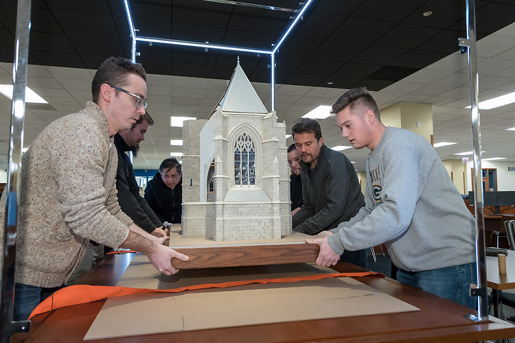 Employees from Presentation Studios International, an architectural and engineering model maker based in Chicago, install a scale model of the Church at Folleville, France, that will be on display on the second floor of the Richardson Library on the Lincoln Park Campus. The church is where on Jan. 25, 1617, St. Vincent de Paul preached a sermon which led to the foundation of the Congregation of the Mission and all of his works. The model captures what the church looked like on that day. The church is still in existence but has undergone many changes over its 500 year history. (DePaul University/Jeff Carrion)