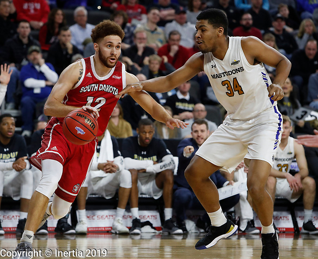 SIOUX FALLS, SD - MARCH 10: Trey Burch-Manning #12 from South Dakota dribbles around Cameron Benford #34 from Purdue Fort Wayne at the 2019 Summit League Basketball Tournament at the Denny Sanford Premier Center in Sioux Falls. (Photo by Dick Carlson/Inertia)