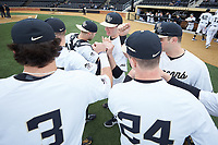 The Wake Forest Demon Deacons huddle up before taking the field against the Sacred Heart Pioneers at David F. Couch Ballpark on February 15, 2019 in  Winston-Salem, North Carolina.  The Demon Deacons defeated the Pioneers 14-1.  (Brian Westerholt/Four Seam Images)