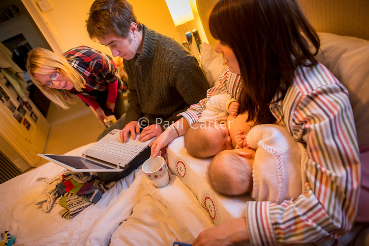 A woman breastfeeding her 5 month old twins at the same time on her bed in her bedroom.  Her husband is sitting next to her working on his computer and her mother-in-law is looking on too.<br /> <br /> Image from the &quot;We Do It In Public&quot; documentary photography project collection: <br />  www.breastfeedinginpublic.co.uk<br /> <br /> Hampshire, England, UK<br /> 11/02/2013
