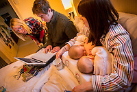 "A woman breastfeeding her 5 month old twins at the same time on her bed in her bedroom.  Her husband is sitting next to her working on his computer and her mother-in-law is looking on too.<br /> <br /> Image from the ""We Do It In Public"" documentary photography project collection: <br />  www.breastfeedinginpublic.co.uk<br /> <br /> Hampshire, England, UK<br /> 11/02/2013"