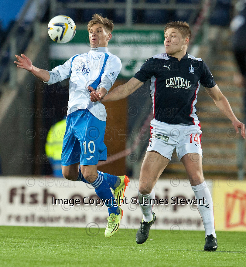 Queen of the South's Gavin Reilly and Falkirk's Peter Grant challenge for the ball.