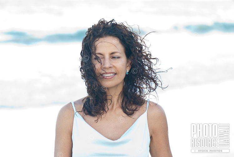 Portrait of woman looking of to left with windy blowing curly hair, age 50 wearing soft blue dress