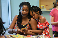 NWA Democrat-Gazette/CHARLIE KAIJO Hannah Morgan, 7, (right) hugs Lisa Morgan (left) of Kansas City, Kan. as they make an art piece during a drop-in art making class, Sunday, July 7, 2019 at Crystal Bridges Museum in Bentonville. <br /> <br /> Guest artist, Michael Albert, showed guests how to make art using upcycled cardboard from discarded consumer packaging. The New York native is on a multi-state tour.