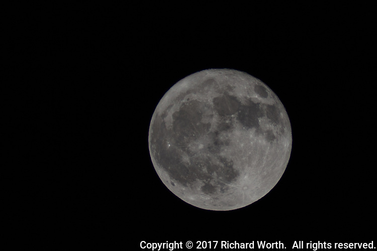 The October 2017 Full Harvest Moon on its journey across the black night sky.