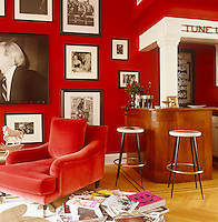 "A compact cocktail bar is situated in one corner of the living room which has been painted a sultry ""lipstick"" red with an armchair in matching velvet upholstery"