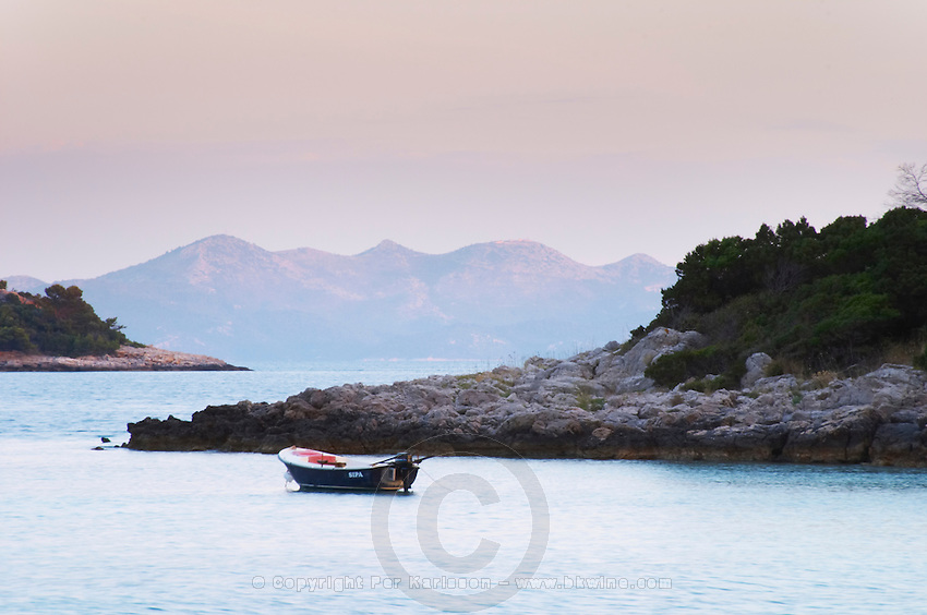 View across the sea to islands and mountains with a small motor pleasure boat moored, off the Korcula island at sunset. Prizba village. Korcula Island. Prizba, Riva Apartments, Danny Franulovic. Korcula Island. Dalmatian Coast, Croatia, Europe.