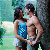 Couple embracing, leaning against a tree&#xA;<br />