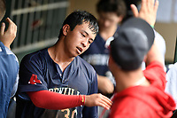 Third baseman Tanner Nishioka (30) of the Greenville Drive is greeted in the dugout after scoring a run in Game 1 of a doubleheader against the Hickory Crawdads on Wednesday, July 25, 2018, at Fluor Field at the West End in Greenville, South Carolina. Greenville won, 4-1. (Tom Priddy/Four Seam Images)