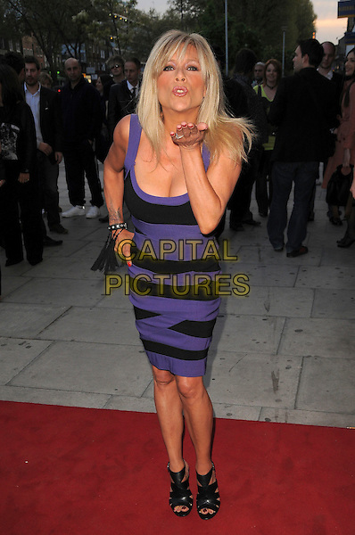 """SAMANTHA FOX.The """"City Rats"""" East End Film Festival VIP Screening, Genesis Cinema, Mile End Road, London, England..April 24th 2009.full length black and purple dress handS on hipS booties sandals shoes bending leaning cleavage sam hand blowing kiss.CAP/CAS.©Bob Cass/Capital Pictures."""